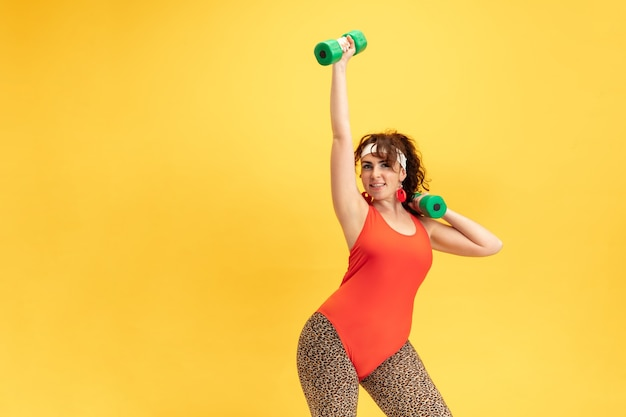 Young caucasian plus size female model's training on yellow background. copyspace. concept of sport, healthy lifestyle, body positive, fashion, style. flexible woman with weights, looks stylish.