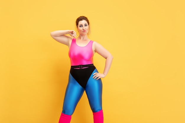 Young caucasian plus size female model's training on yellow background. copyspace. concept of sport, healthy lifestyle, body positive, fashion, style. stylish woman posing confident and cool.