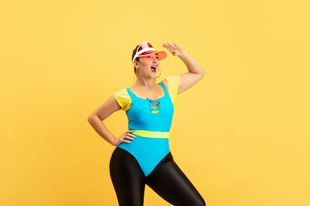 Young caucasian plus size female model's training on yellow background. copyspace. concept of sport, healthy lifestyle, body positive, fashion, style. stylish woman posing confident in red hat.