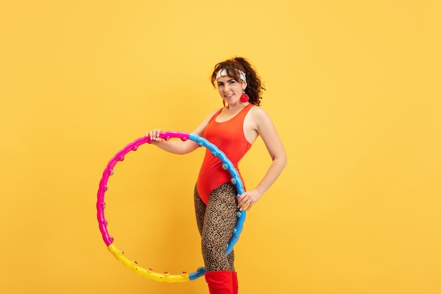 Young caucasian plus size female model's training on yellow background. copyspace. concept of sport, healthy lifestyle, body positive, fashion, style. stylish woman practicing, posing with hoop.