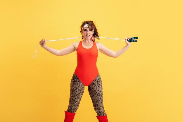 Young caucasian plus size female model's training on yellow background. copyspace. concept of sport, healthy lifestyle, body positive, fashion, style. stylish woman practicing with jump rope.