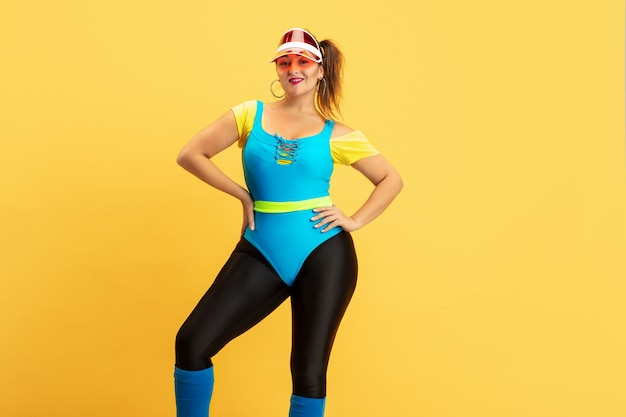 Young caucasian plus size female model's training on yellow wall. copyspace. concept of sport, healthy lifestyle, body positive, fashion, style. stylish woman posing confident in red hat.