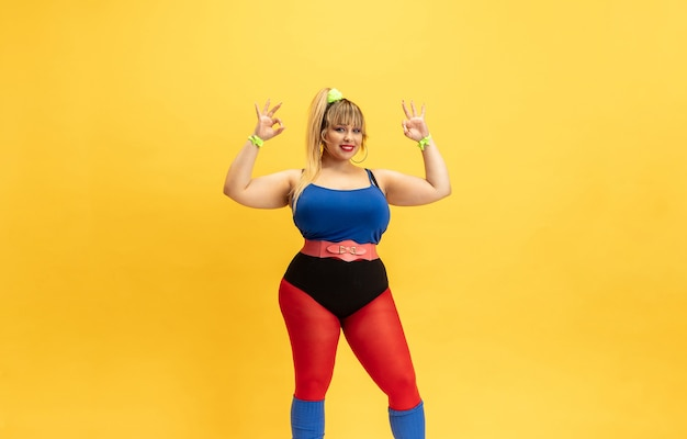 Young caucasian plus size female model's training on yellow wall. stylish woman in bright clothes. copyspace. concept of sport, healthy lifestyle, body positive, fashion. smiling, showing nice.