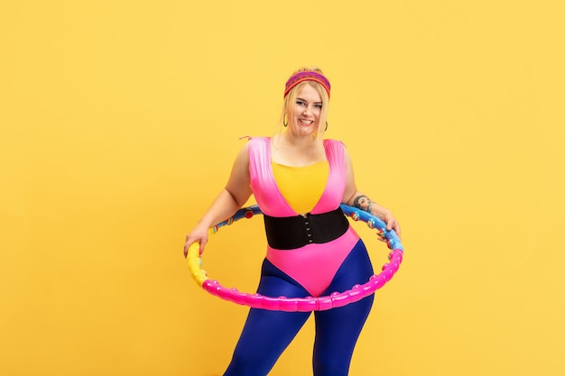 Young caucasian plus size female model's training on yellow