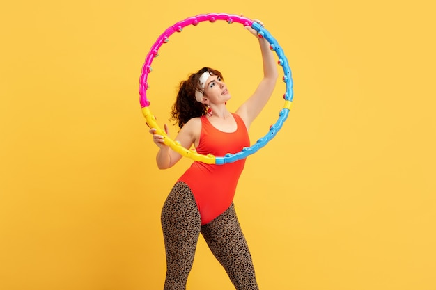 Formazione del giovane modello femminile caucasico plus size su giallo