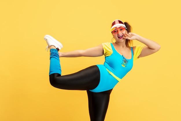 Молодая кавказская модель большого размера тренируется на желтом