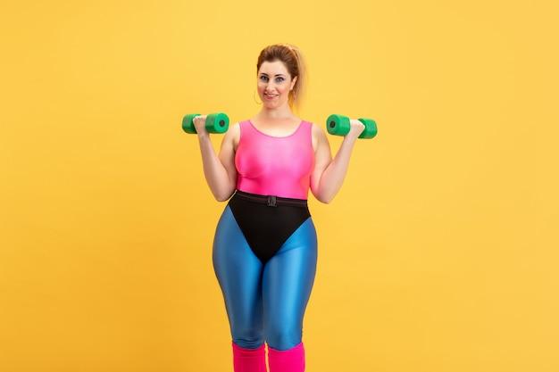黄色の若い白人プラスサイズの女性モデルのトレーニング 無料写真