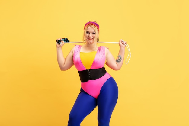 Young caucasian plus size female model training on yellow