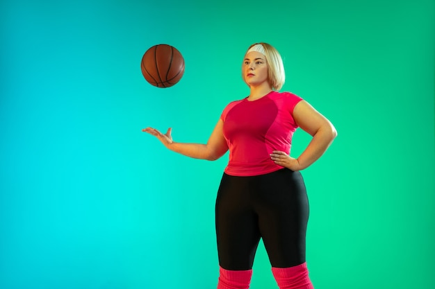 グラデーショングリーンでトレーニングする若い白人プラスサイズの女性モデル