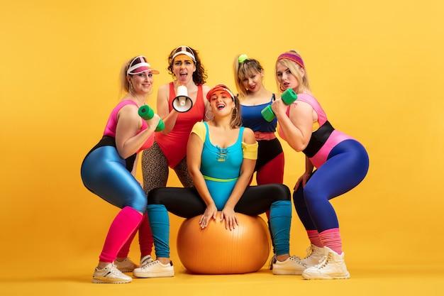 노란색 벽에 젊은 백인 더하기 크기 여성 모델 교육. copyspace. 스포츠, 건강한 라이프 스타일, 신체 긍정적, 패션의 개념. 우정, 소녀의 힘. 포즈, 웃 고 세련 된 여자입니다.