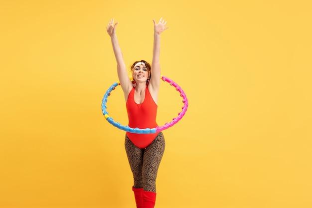 노란색에 훈련 하는 젊은 백인 플러스 사이즈 여성 모델