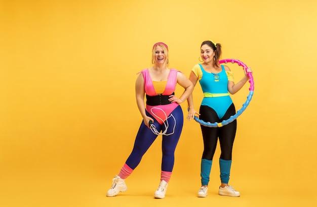 Giovani caucasici plus size modelli femminili formazione sulla parete gialla