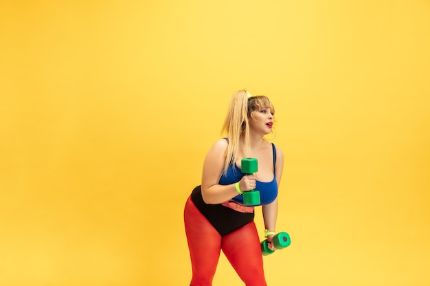 Young caucasian plus size female models training on yellow wall