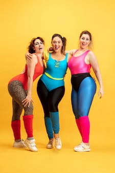 Young caucasian plus size female models training on yellow
