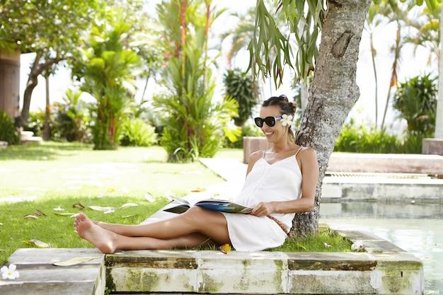 Giovane femmina incinta caucasica in tonalità alla moda che si nasconde dal sole in ombra sotto l'albero, sorridendo felicemente durante la lettura della rivista.