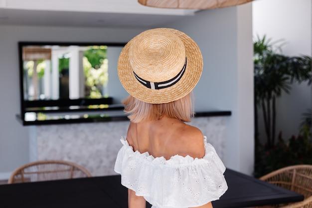 Giovane donna caucasica capelli abbastanza biondi in cucina all'aperto in villa