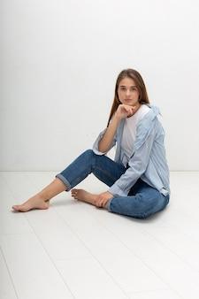 シャツに長い髪の若い白人のかわいい女の子、ブルージーンズはスタジオに座っています