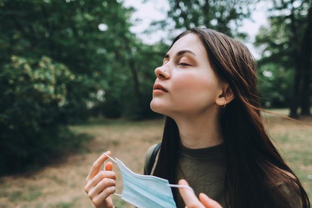 若い白人のきれいな女性は、自然の顔から医療用保護マスクを外し、きれいな新鮮な空気を吸います。