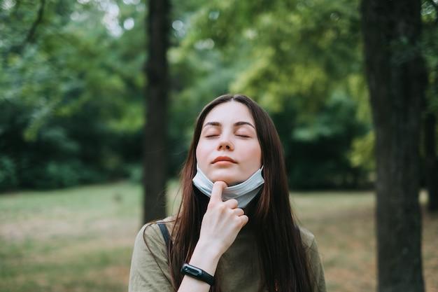Молодая кавказская симпатичная женщина снимает медицинскую защитную маску на природе, вдыхая чистый свежий воздух.
