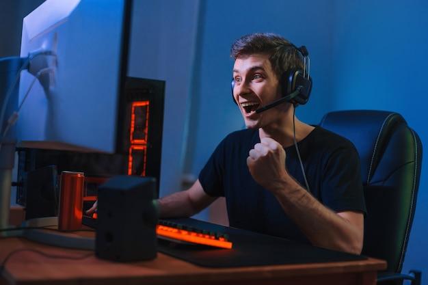 若い白人プロゲーマーはオンラインビデオゲームで勝ち、幸せを感じて終了し、yesの手のジェスチャーを示します。