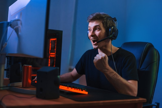 Young caucasian pro gamer win in online video game, feels happy and exited, show yes hand gesture.