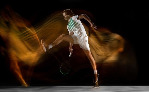 Giovane atleta professionista caucasico giocando a tennis sulla parete nera in luce mista