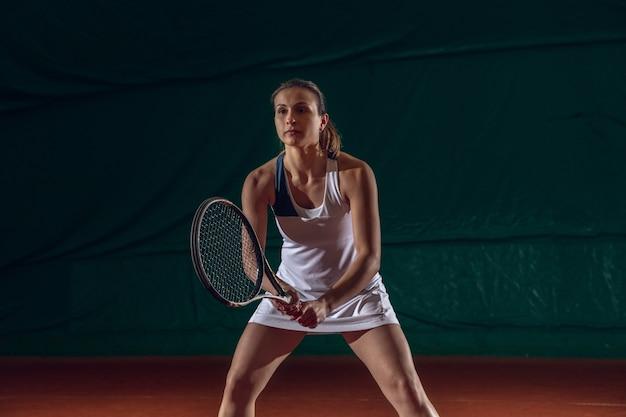スポーツコートの壁でテニスをしている若い白人プロスポーツウーマン。トレーニング、運動の練習、行動。パワーとエネルギー。動き、広告、スポーツ、健康的なライフスタイルのコンセプト。正面図。 無料写真