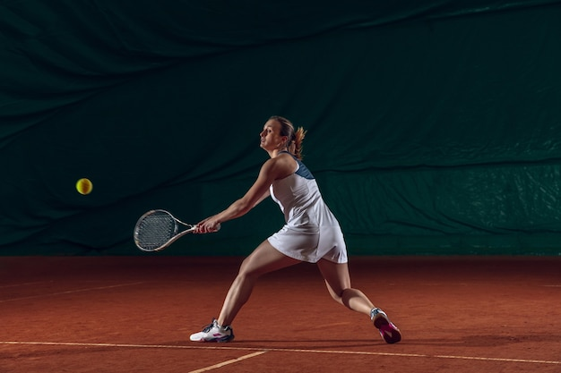 スポーツコートの壁でテニスをしている若い白人プロスポーツウーマン。