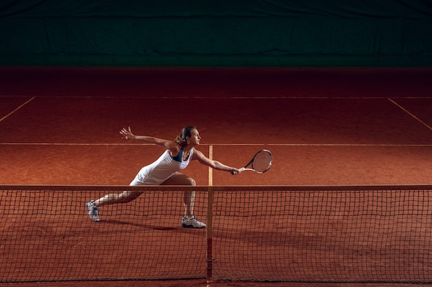 Young caucasian professional sportswoman playing tennis on sport court wall.