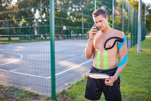 Young caucasian professional tennis player with kinesiology taping on body carrying racket near fenced sports ground. confident man with muscular naked torso talking using smartphone.
