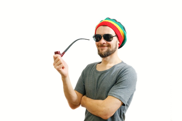 Young caucasian rasta in jamaica hat and grey tshirt on white background with smoke pipe in hand