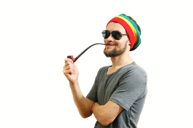 Young caucasian rasta man in jamaica hat sunglasses and grey tshirt with smoke pipe in hand