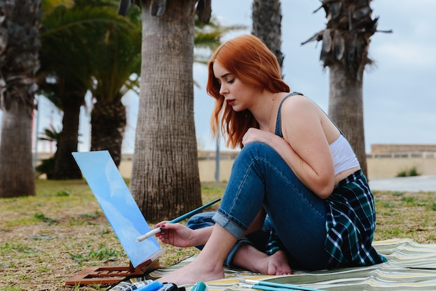 Young caucasian redhead female artist paints a canvas on a small easel with a brush in the park outdoors