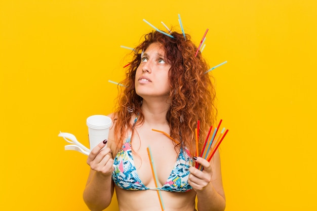 Young caucasian redhead woman angry with the abusive use of plastic