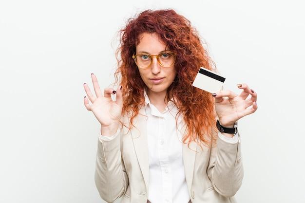 Молодая кавказская рыжая женщина, держащая кредитную карту, жизнерадостная и уверенная, показывая одобренный жест.