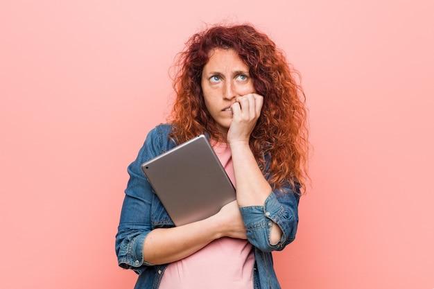 神経質で非常に不安な、爪を噛むタブレットを持っている若い白人赤毛の女性。