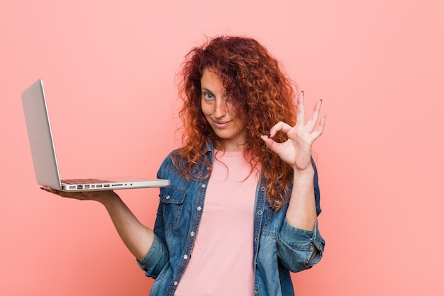 Young caucasian redhead woman holding a laptop cheerful and confident showing ok gesture.