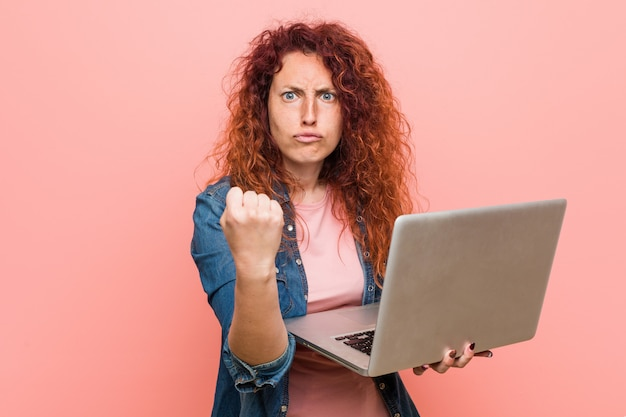 Young caucasian redhead woman holding a laptop showing fist to camera, aggressive facial expression.