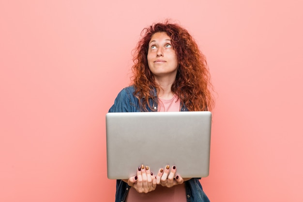 Young caucasian redhead woman holding a laptop smiling confident with crossed arms.