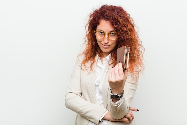Young caucasian redhead woman holding a wallet pointing with finger at you as if inviting come closer