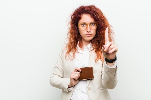 Young caucasian redhead woman holding a wallet showing number one with finger.