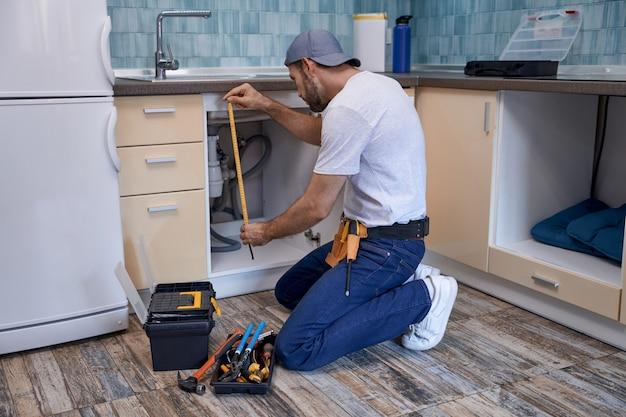 シンクの下の台所の引き出しを測定する若い白人の修理工