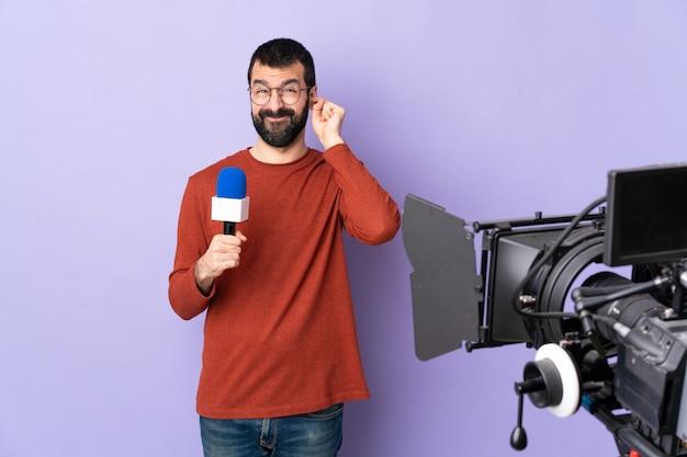 Молодой кавказский репортер над изолированной фиолетовой стеной