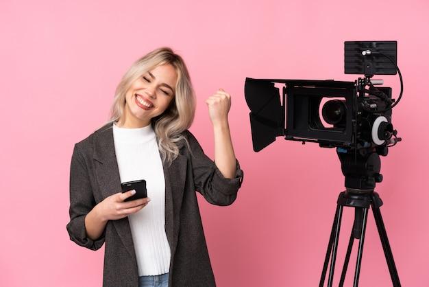 孤立したピンクの壁を越えて若い白人記者女性