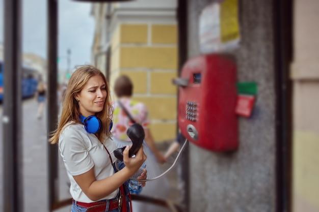 약 20 세 금발 머리를 가진 젊은 백인 슬픈 아름다운 여성은 공중 전화로 회담을 시도하고 있습니다.