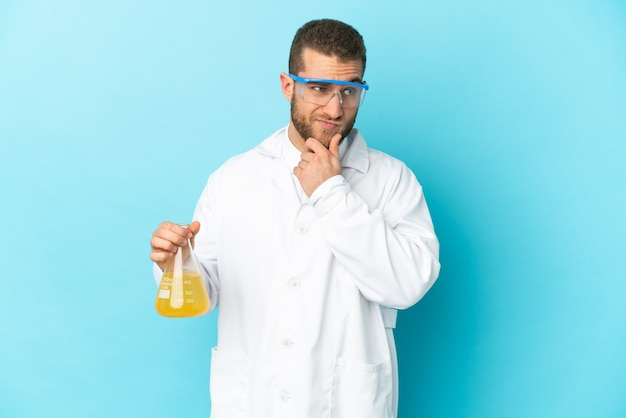 Young caucasian scientific man isolated on blue having doubts and thinking