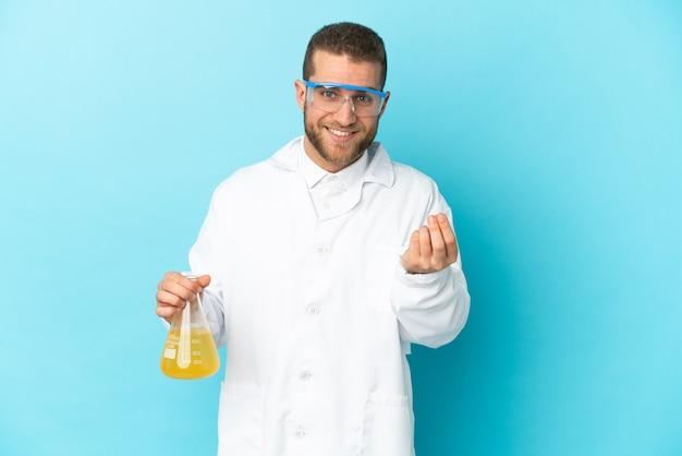 お金のジェスチャーを稼ぐ青い壁に孤立した若い白人科学者