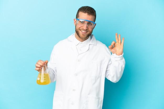 指でokサインを示す青い壁に分離された若い白人科学者