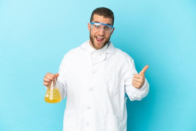 何か良いことが起こったので、親指を立てて青い壁に孤立した若い白人科学者