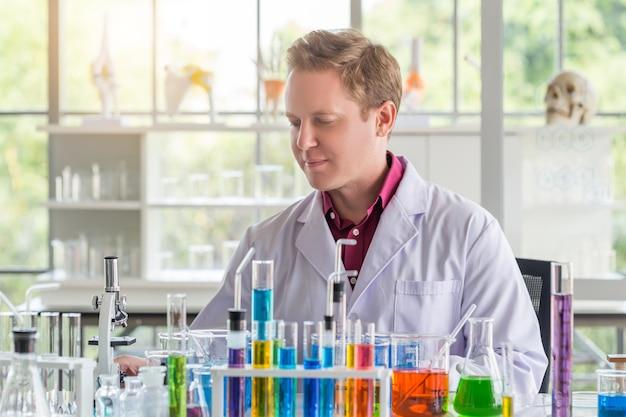 若い白人の科学者が、科学研究所で研究をしながら、試験管を使ってテストを行っています。